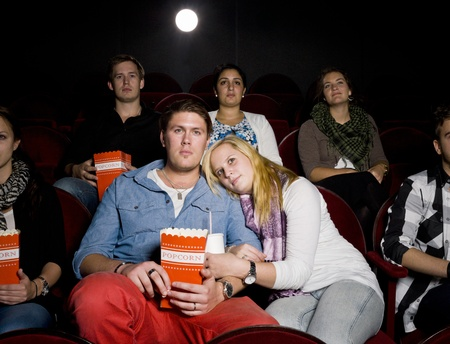 intoxicating: Young Couple at the Movie Theater eating popcorn