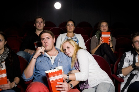 Young Couple at the Movie Theater eating popcorn photo