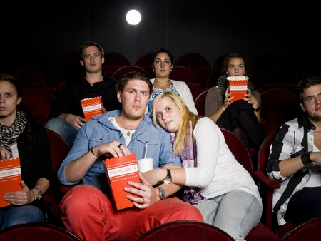 intoxicating: Young Scared Couple at the Movie Theater eating popcorn