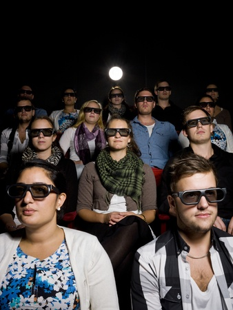 alone in crowd: People at the movie Theater wearing 3d glasses