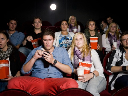 Mindless man with cellphone together with his girlfriend at the movie theater