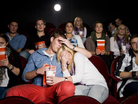 first date: Young Scared Couple at the Movie Theater eating popcorn
