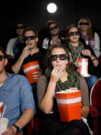 Spectators eating popcorn at the movie theater photo