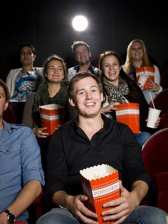 intoxicating: Young man at the movie theater with bag of popcorn Stock Photo