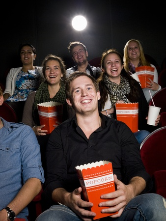 Young man at the movie theater with bag of popcorn photo