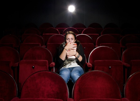 alone in crowd: Afraid young woman alone in the movie theater