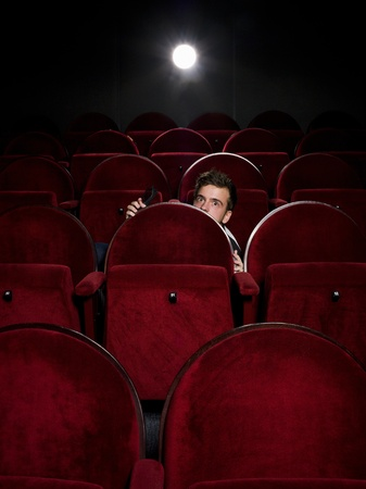 Afraid young man alone in the movie theater photo