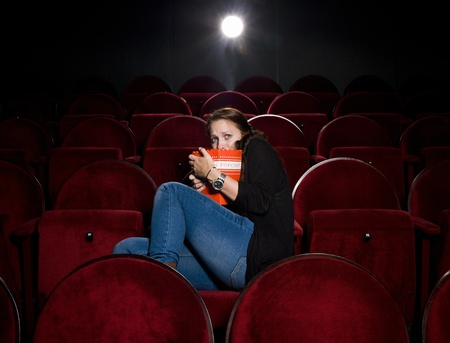 Afraid young woman alone in the movie theater Stock Photo - 10740657