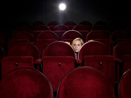 Afraid young woman alone in the movie theater photo