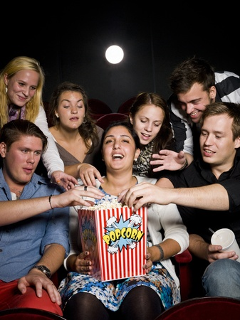 intoxicating: Group of young spectators eating popcorn at the movie theater