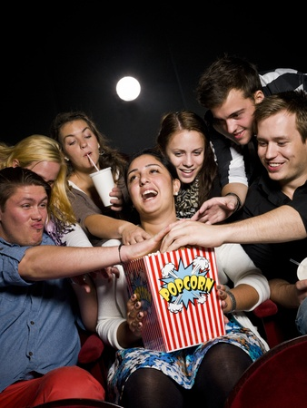 Group of young spectators eating popcorn at the movie theater photo