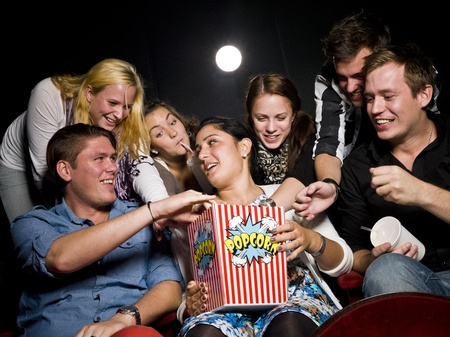 Movie theater: Group of young spectators eating popcorn at the movie theater