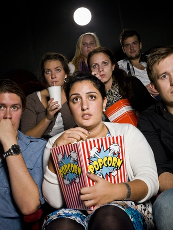 Afraid young woman at the movie theater with bag of popcorn photo