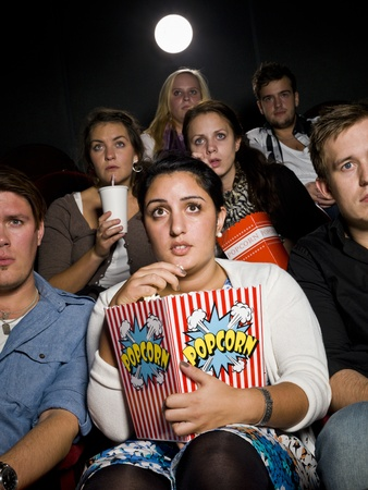 crowd cheering: Afraid young woman at the movie theater with bag of popcorn