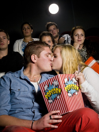 alone in crowd: Young couple on a date at the movie theater