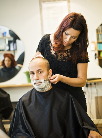 barbers: Shaving situation at the hair salon Stock Photo
