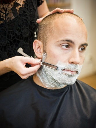 barber shave: Adult man being shaved at the hair salon