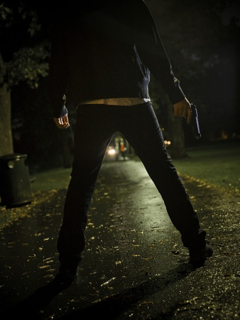 Man threating two women with a gun at night photo