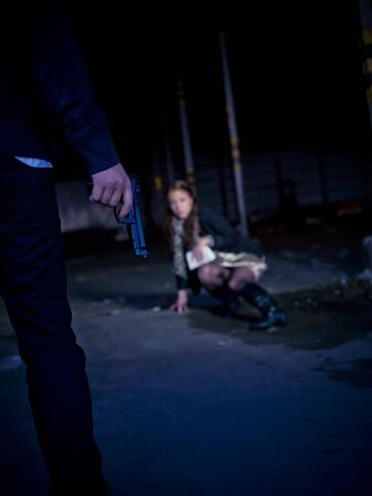 Man threating a woman with a gun at night photo