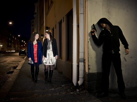 obscured: Hooded man stalking two women behind a corner holding a gun