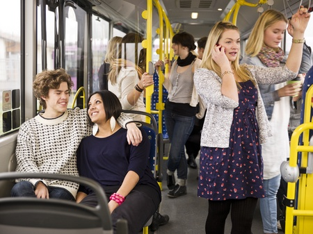 love seat: Happy couple going by bus with large group of people