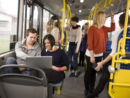 commuters: Couple with computer going by bus