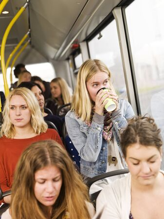 coffee hour: Woman drinking coffee on the bus Stock Photo