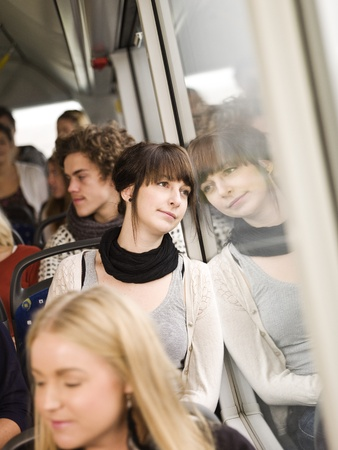 commuters: Young woman on the bus with large group of people