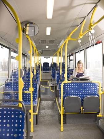 Lonely woman on the bus reading a newspaper Stock Photo - 11533776
