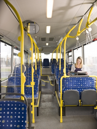 vacant: Lonely woman on the bus reading a newspaper Stock Photo