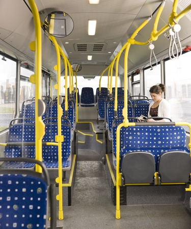 Young woman with a book alone on the bus photo