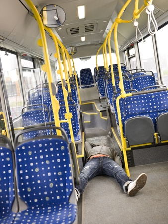 Young man lieing on the floor on the bus photo