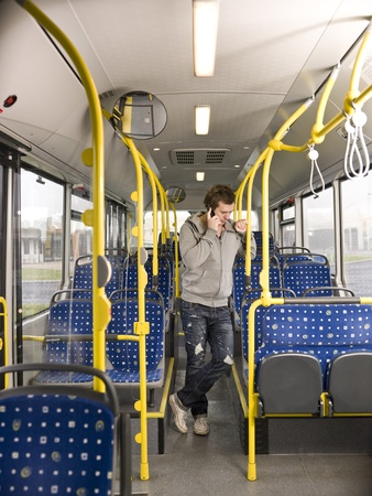 Young man on the phone going by bus photo