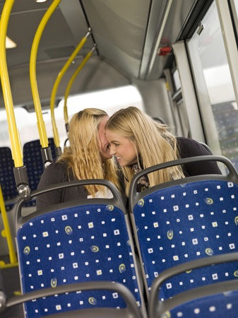 Two young women wispering secrets on the busn photo