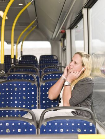 Young woman alone on the bus listen to music photo