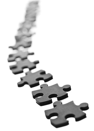 the bigger picture: Black Jigsaw pieces in a row isolated on white