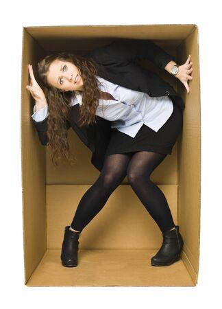 Mujer joven en el interior de una caja de cartón fuerte