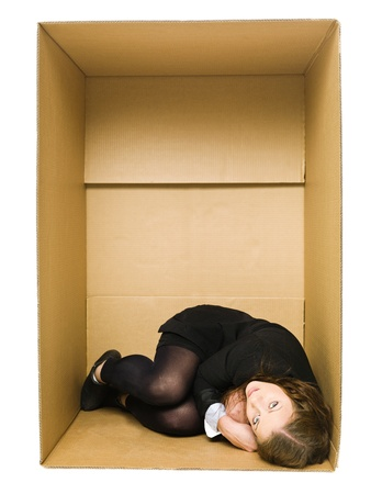 confined space: Woman in a Cardboard Box isolated on white Background Stock Photo