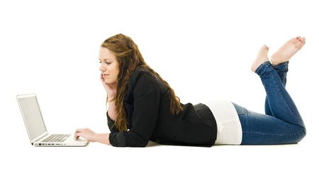 Woman on the floor with a laptop isolated photo