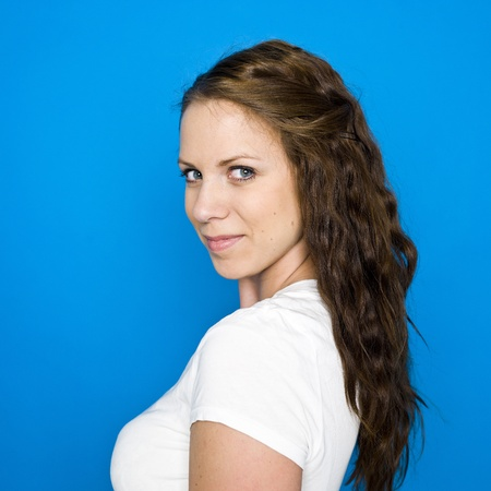 sideview: Portrait of a young girl on blue background