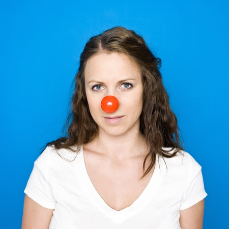 clown nose: Portrait of a young girl on blue background