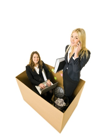 Two Business women in a very small Cardboard office isolated on white background Stock Photo - 11741086