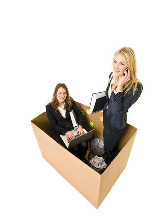 Two Business women in a very small Cardboard office isolated on white background photo