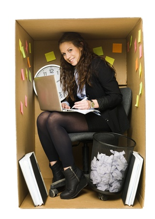 office chaos: Businesswoman in a very small Cardboard Office isolated on white background