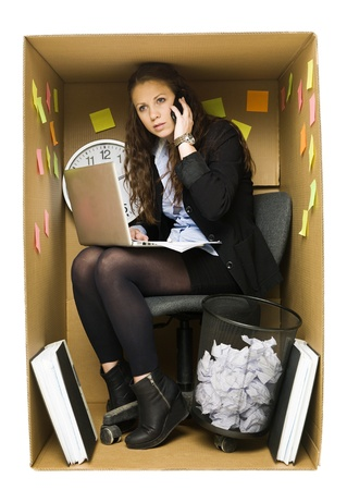 Businesswoman in a very small Cardboard Office isolated on white background photo