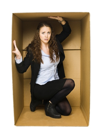 trapped: Woman in a cardboard box isolated on white background Stock Photo