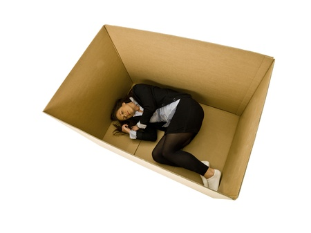 Woman sleeping in a cardboard box isolated on white background