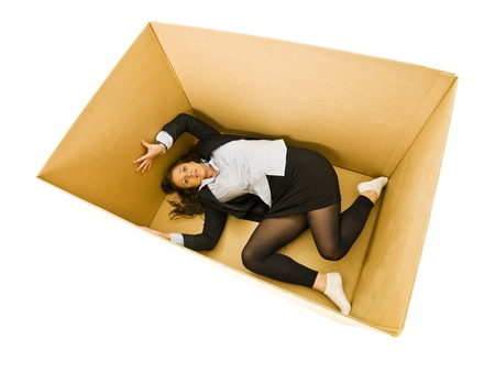 trapped: Afraid Woman in a cardboard box isolated on white background Stock Photo