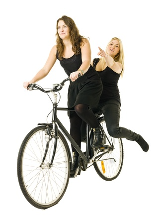 Two women on a bicycle isolated on white background photo