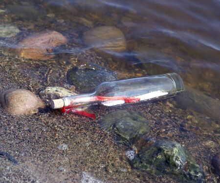 Message in a bottle at the edge of the water photo
